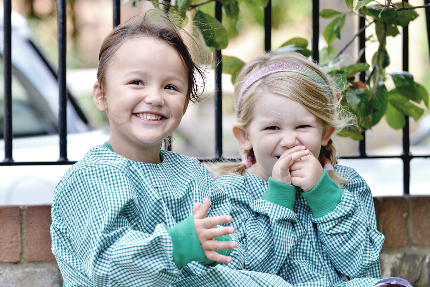 Two nursery girls laughing together