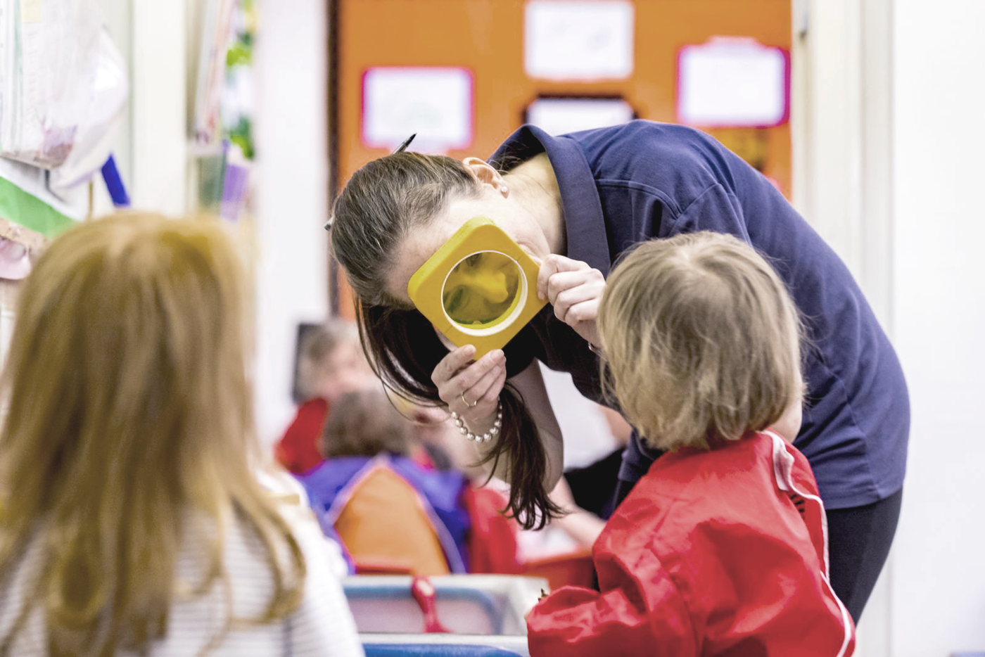 Nursery teacher looking thorugh colourful lens at child
