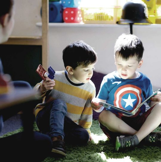 Two boys at twickenham park day nursery reading a book