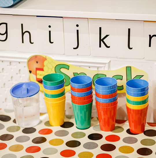 Colourful cups and the alphabet on a spotty tablecloth