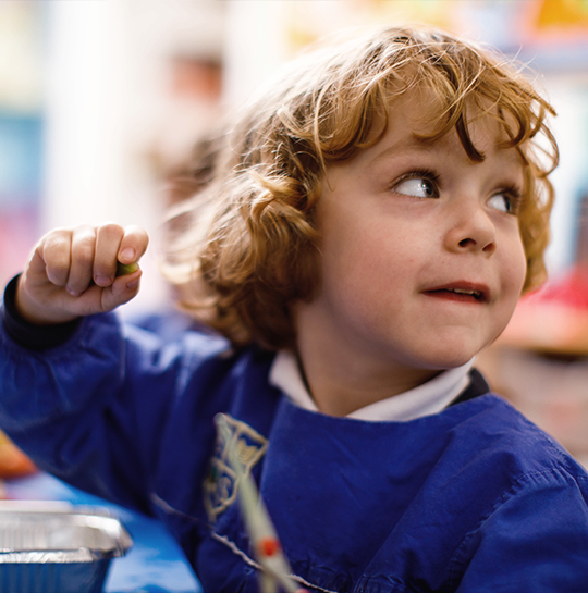 Young boy with curly gold hair turning round to ask the teacher a question at nursery