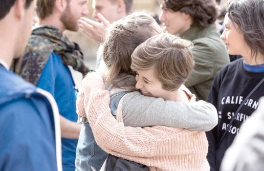 two summer school students standing in a group and hugging