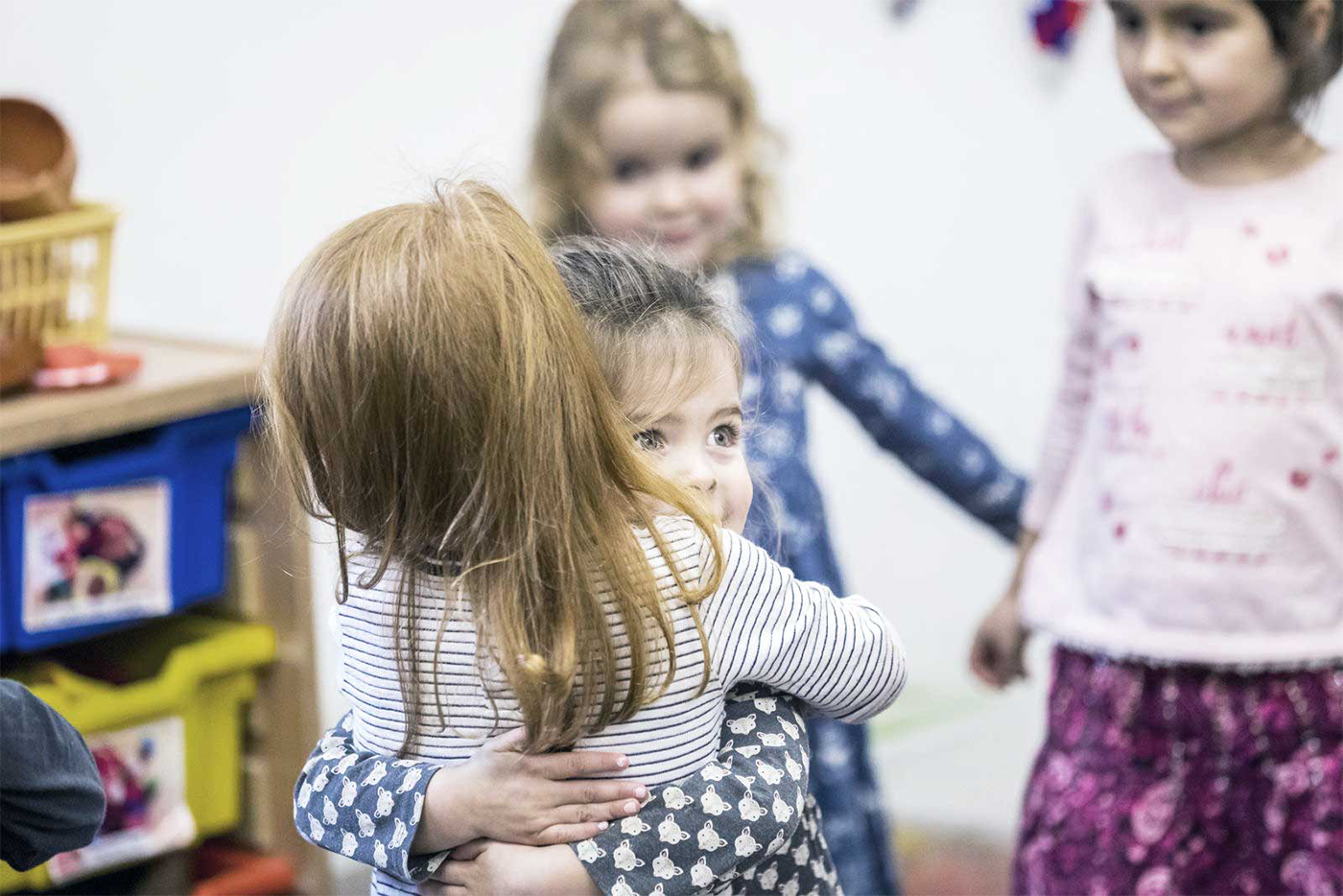 Little girls hugging in nursery