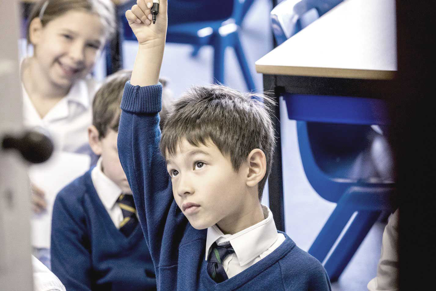 boy in class raising his hand