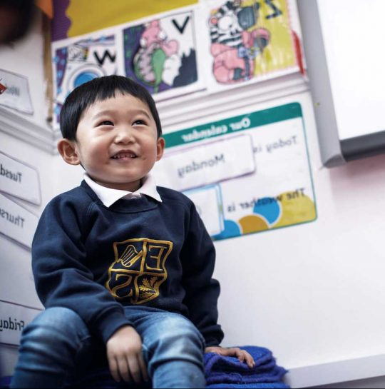Eaton square nursery boy sitting in classroom smiling