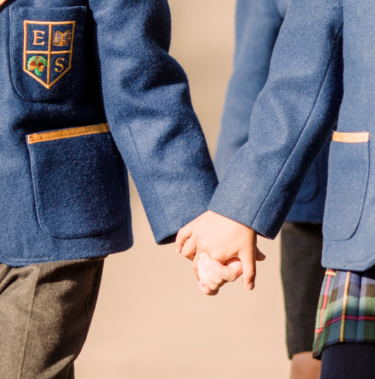 Boy and girl hold hands in Eaton Square school uniform