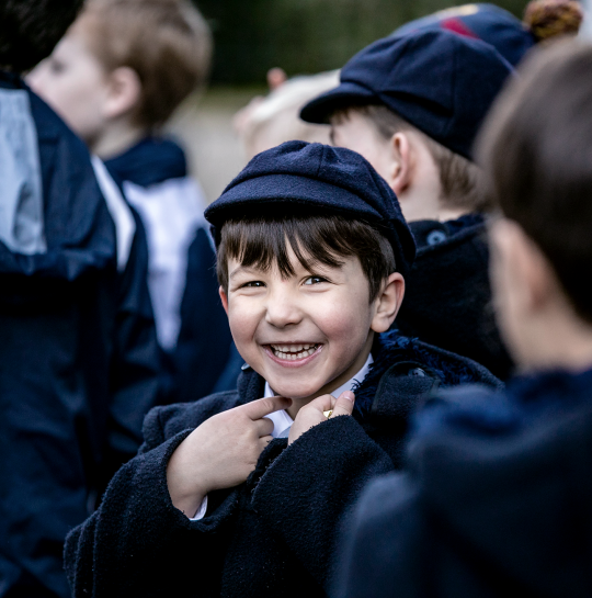 Little boy in school uniform in a crowd turning round smiling