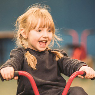Tot with pigtail plaits playing on tricycle