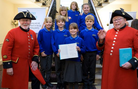Students and Royal Chelsea Pensioners holding a certificate