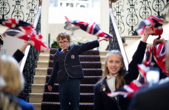 school children waving UK flags